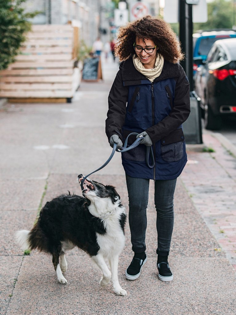 A woman wearing a Burton Prowess jacket walking her dog.