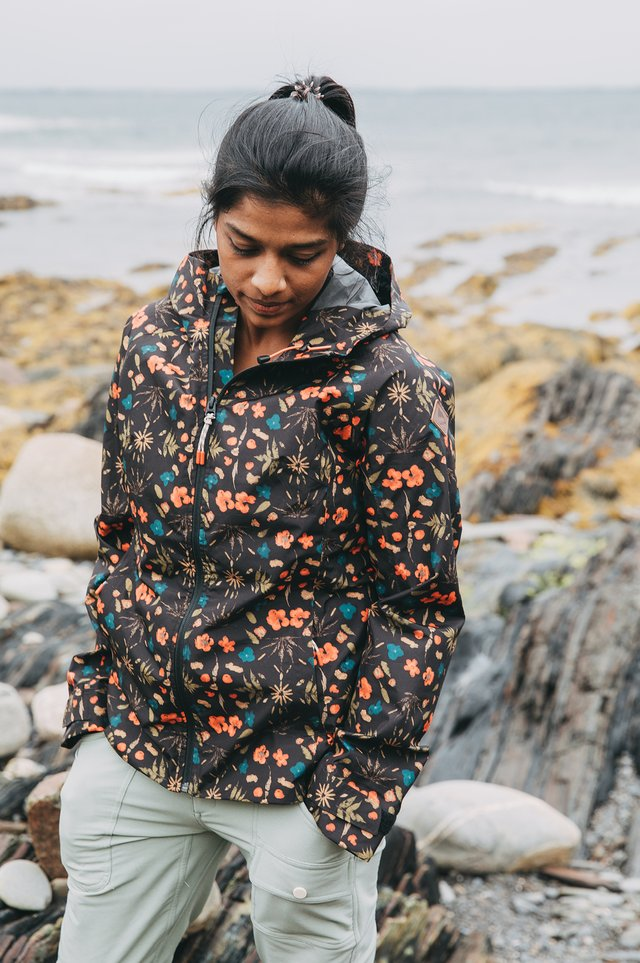 A woman walking on the beach in a rain jacket.